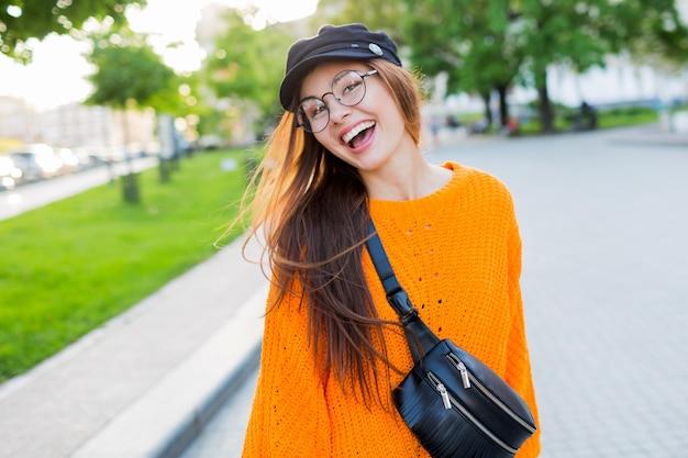 Lebensstilporträt der schönen frau mit erstaunlichen langen brünetten windigen haaren, die spaziergang im park genießen.