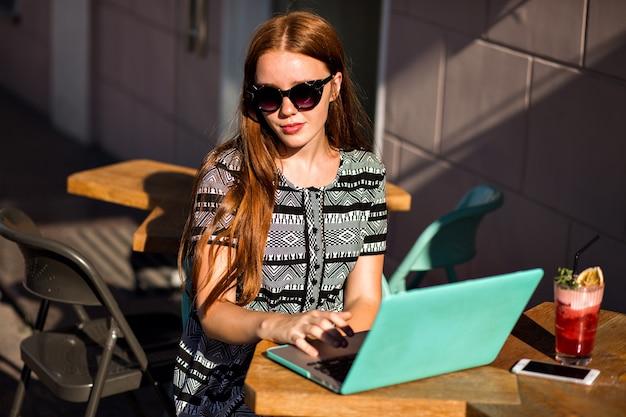 Lebensstilporträt des hübschen studenten-rothaarigen mädchens, das an der caféterrasse sitzt und ihren laptop benutzt