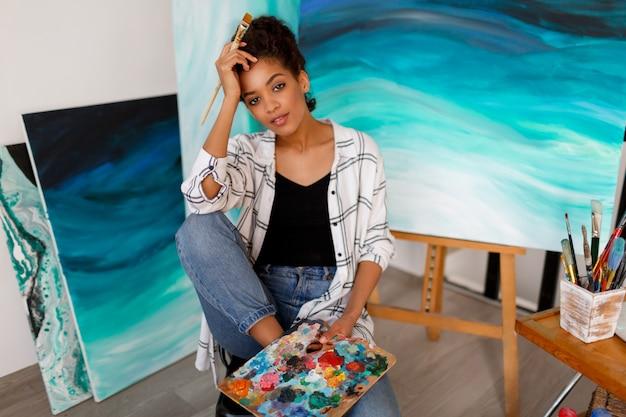 Lebensstilporträt des jungen afrikanischen studenten, der mit erstaunlicher abstrakter handacrylkunst des abstrakten meeresacryl im studio sitzt.