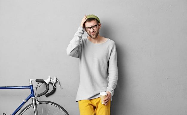 Lebensstilporträt des modischen jungen mannes mit bart, der schmerzhaften blick wegen der kopfschmerzen hat, isoliert an grauer wand mit festem gangfahrrad steht und papierbecher hält, kaffee trinkt, um zu gehen