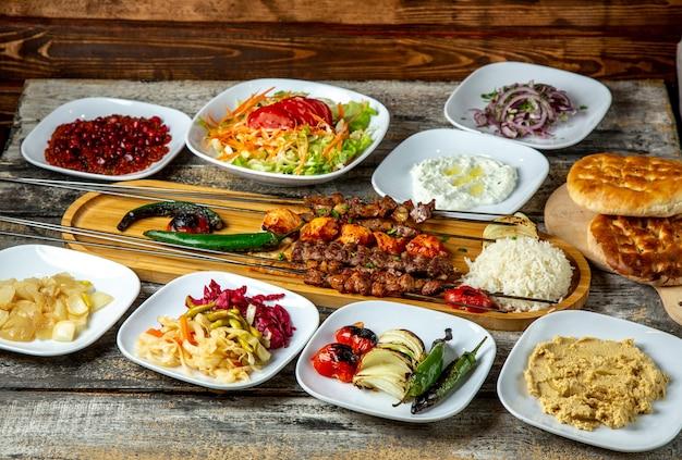 Leber kebab mit hummus essiggurken gemüse reis seitenansicht