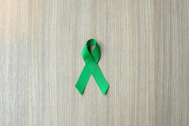 Leber-krebs-bewusstsein, grünes band auf hölzernem hintergrund