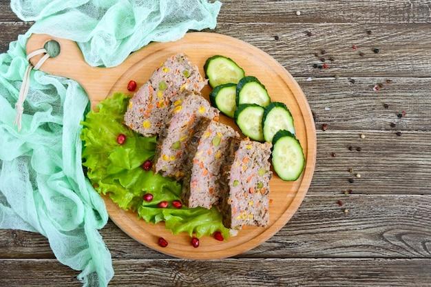 Leberauflauf. nützliches gericht aus der leber. frisch gebackene schweineleber souffle mit reis und gemüse auf einem holztisch.
