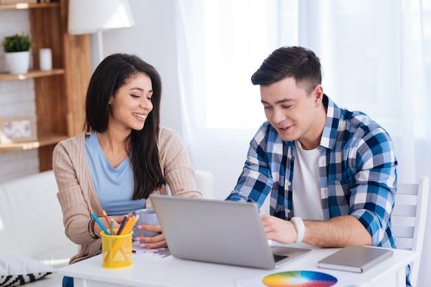 Lebhafte diskussion. positives attraktives paar, das bildschirm betrachtet, während mann laptop verwendet