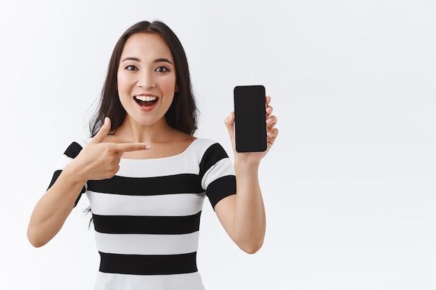 Lebhafte, enthusiastische junge asiatin stellt aufgeregt eine tolle neue anwendung vor, teilt lieblingsvideos oder -fotos, beschreibt ihren urlaub einem freund als zeigendes smartphone-display und lächelt freudig