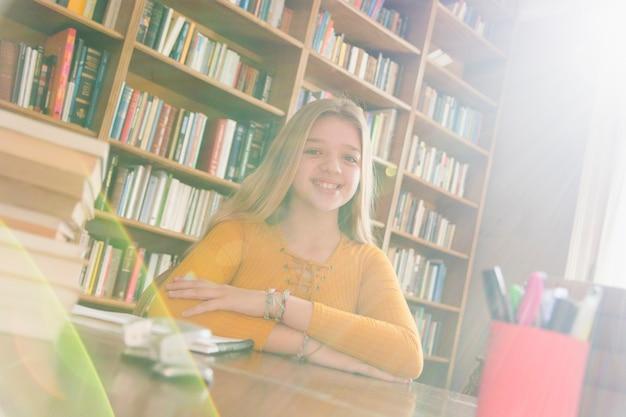 Lebhafte intelligente jugendliche, die in der bibliothek sitzt