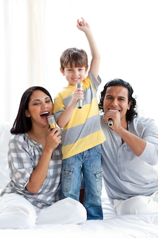 Lebhafte junge familie, die mit mikrophonen singt
