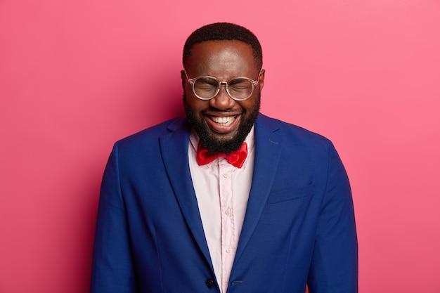 Lebhafter fröhlicher schwarzer mann hält die augen geschlossen, kichert positiv, genießt aufregende büroparty, drückt positive gefühle aus, trägt einen formellen anzug