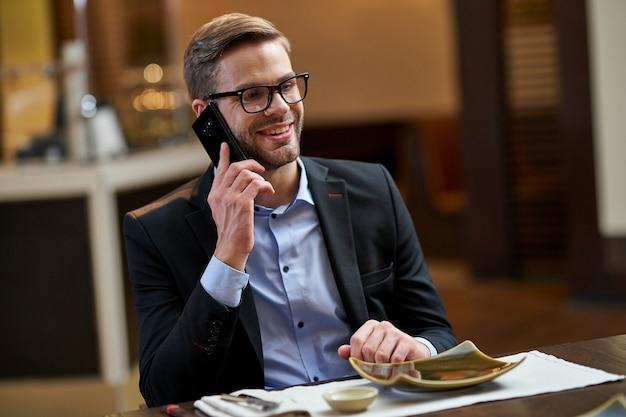 Lebhafter geschäftsspezialist, der an einem holztisch im restaurant sitzt und einen anruf mit einem lächeln beantwortet