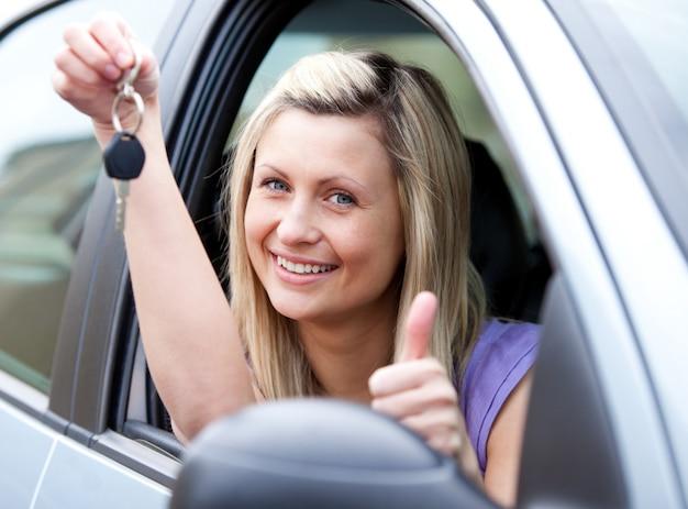Lebhafter weiblicher fahrer, der einen schlüssel zeigt, nachdem ein neues auto geblieben ist