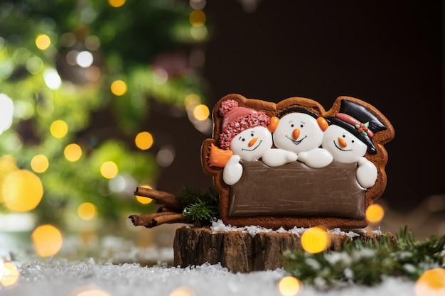 Lebkuchen drei lustige schneemänner in gemütlicher warmer dekoration mit girlandenlichtern