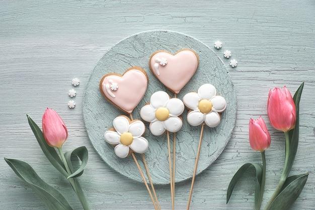 Lebkuchen geformt als herzen und blumen mit frischen rosa blumen auf hellem strukturiertem holz