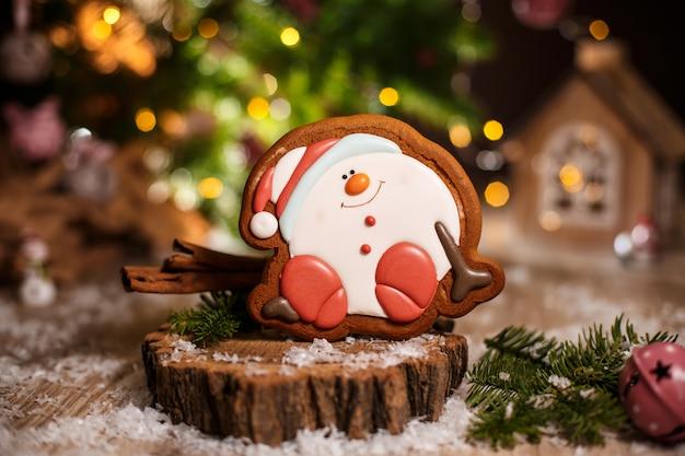 Lebkuchen glücklich sitzender schneemann oder schneeball in gemütlicher warmer dekoration mit girlandenlichtern