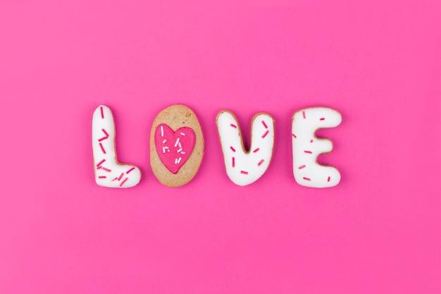 Lebkuchen in form des wortes liebe auf rosa hintergrund. flache lage, ansicht von oben.