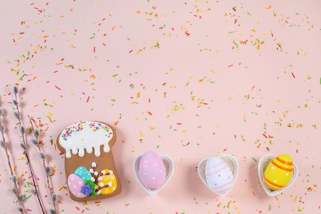 Lebkuchen in form eines osterkuchens und bunter eier auf einem hellen schreibtisch