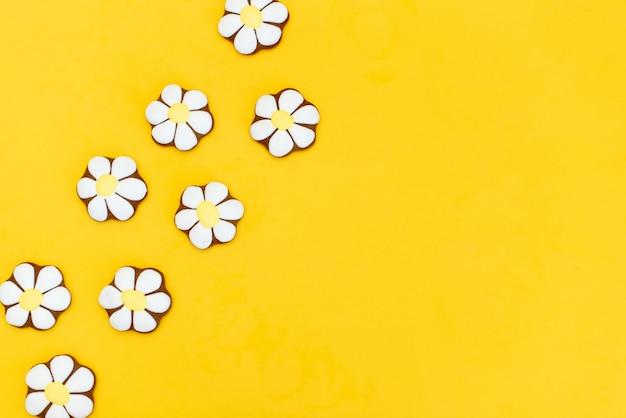 Lebkuchen in form von gänseblümchen auf gelb