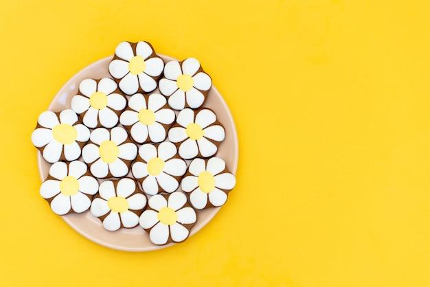 Lebkuchen in form von gänseblümchen auf gelb.