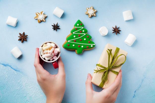 Lebkuchen in form von weihnachtsbäumen auf einem blau, eine tasse heiße schokolade und süßigkeiten in kinderhänden.