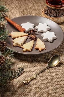 Lebkuchen in weihnachtsbaum- und sternform auf teller mit zimt, sternanis und natürlichen tannenzweigen mit zapfen und löffel, tasse kaffee auf dem tisch mit sackleinen.