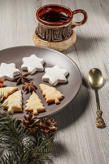 Lebkuchen in weihnachtsbaum- und sternform auf teller mit zimt, sternanis und natürlichen tannenzweigen mit zapfen und tasse kaffee auf grauem hintergrund