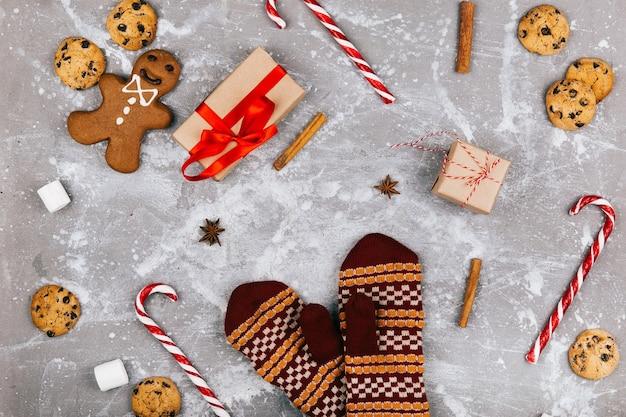 Lebkuchen, kekse, marshmallows, rote weiße knödel, zimt, andere gewürze, geschenkschachtel liegen um warme handschuhe herum