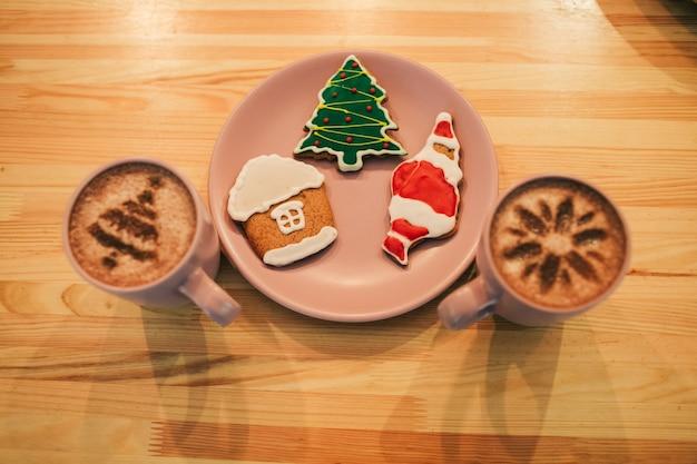 Lebkuchen mit weihnachts-design liegen auf rosa teller zwischen tassen mit kaffee