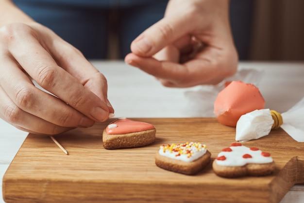 Lebkuchen mit zuckerguss verzieren. frauenhände verzieren plätzchen in form des herzens, nahaufnahme
