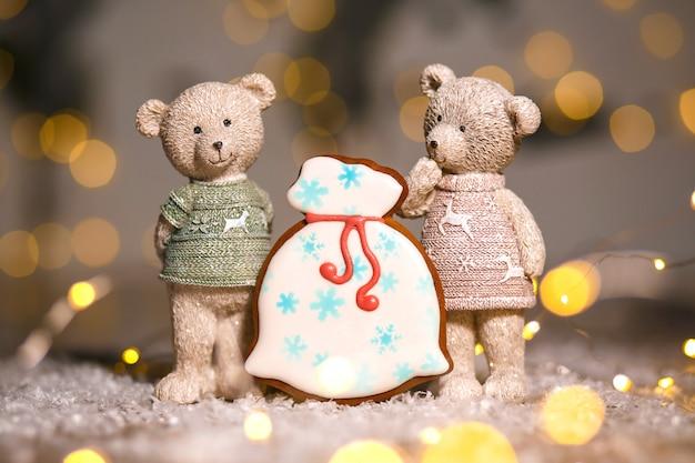Lebkuchen santa tasche mit geschenken und zwei dekorativen bären in gemütlicher, warmer dekoration mit girlandenlichtern