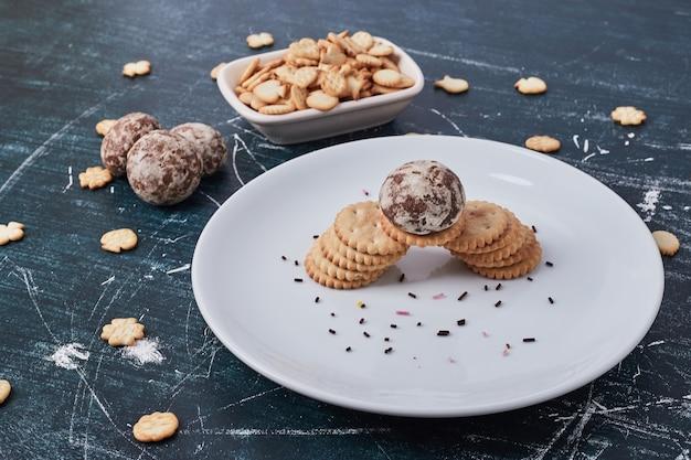 Lebkuchen und cracker in einem weißen teller auf blau.