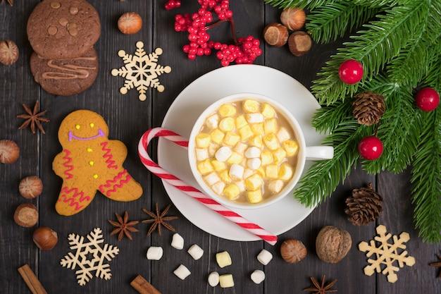 Lebkuchen und heiße schokolade mit marshmallows, zimt auf holztisch verziert