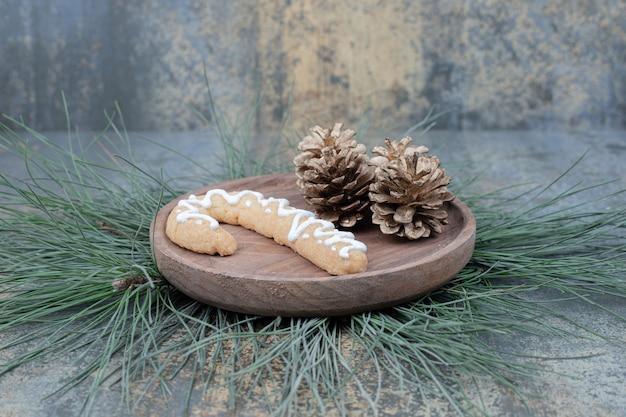 Lebkuchen und tannenzapfen auf holzteller. hochwertiges foto