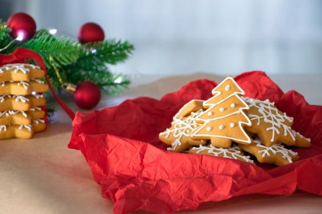 Lebkuchen-weihnachtsbaum und sterne in der roten serviette mit tannenzweigen und roten spielzeugen
