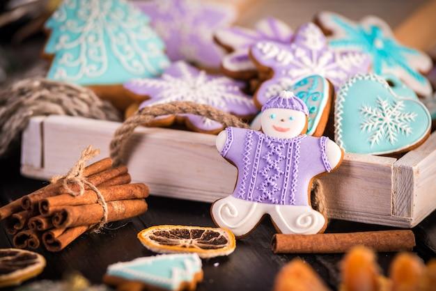 Lebkuchen weihnachtsplätzchen, schneeflocken ein gingerman. gestrickter schal und zimtstangen.