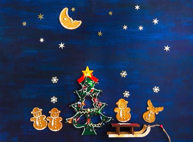 Lebkuchen-weihnachtsplätzchen und spielzeug-weihnachtsbaum auf einem dunkelblauen hintergrund. flaches layout