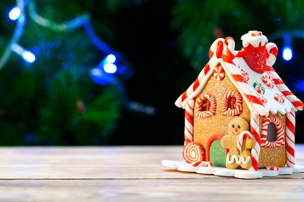 Lebkuchenhaus auf einem holztisch gegen den eines weihnachtsbaumes.