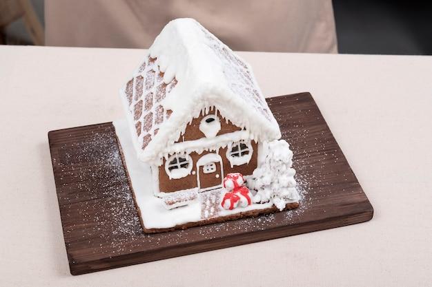 Lebkuchenhaus auf holzküchenbrett draufsicht. traditionelles weihnachtsbacken.
