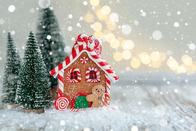 Lebkuchenhaus auf weißem holzhintergrund mit defokussierten lichtern und schnee. weihnachtsstimmung konzept.