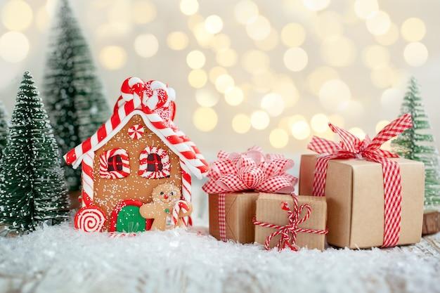 Lebkuchenhaus mit vielen geschenkboxen auf holzhintergrund. symbol für weihnachts- und winterferien.