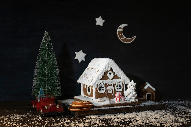 Lebkuchenhaus neben spielzeugauto und weihnachtsbaum. frohe weihnachten und ein glückliches neues jahr.