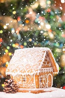 Lebkuchenhaus über defokussierten lichtern von chrismtas dekoriertem tannenbaum und schnee