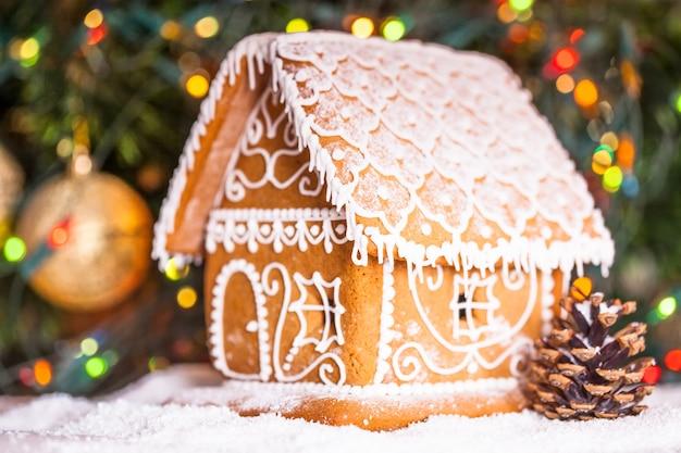 Lebkuchenhaus über defokussierten lichtern von chrismtas dekoriertem tannenbaum