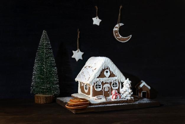 Lebkuchenhaus und kleiner weihnachtsbaum auf dunklem hintergrund. weihnachtskomposition.