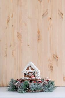 Lebkuchenhaus und weihnachtskranz auf hellem hölzernem hintergrund. speicherplatz kopieren.