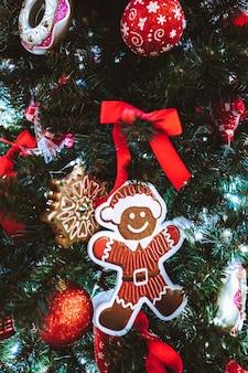 Lebkuchenmann hängt am weihnachtsbaum holiday party dekoration oder postkartenkonzept