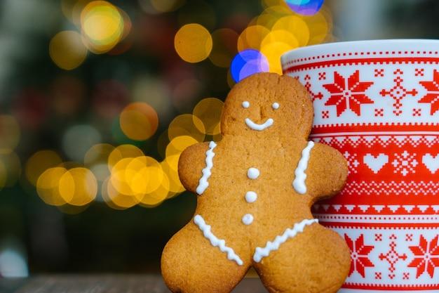 Lebkuchenmann und roter becher mit weihnachtsverzierung