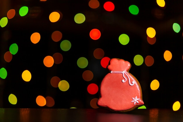 Lebkuchenplätzchen der roten tasche sankt mit geschenken über defocused farbigen lichtern der girlande.