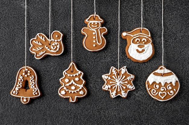 Lebkuchenplätzchen der weihnachtsbaumdekoration auf schwarzem hintergrund