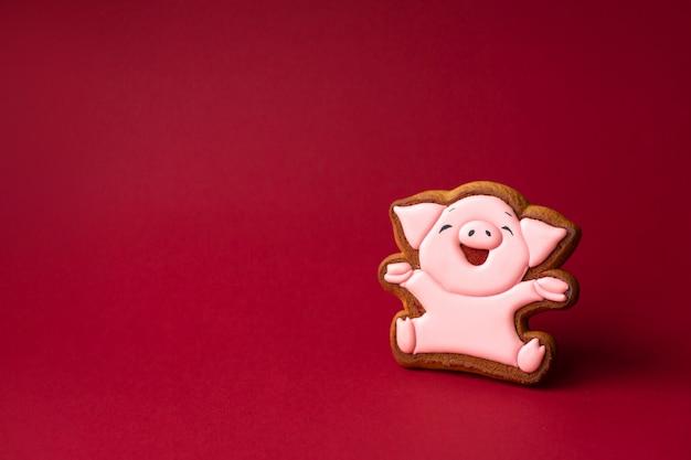 Lebkuchenplätzchen des netten rosa schweins auf rotem copyspace