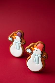 Lebkuchenplätzchen des netten schneemanns auf rot. traditionelles weihnachtsessen. weihnachten und neujahr.