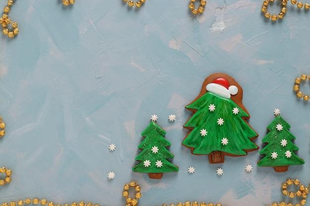 Lebkuchenplätzchen geformte weihnachtsbäume auf hellblauem hintergrund, ansicht von oben, nahaufnahme